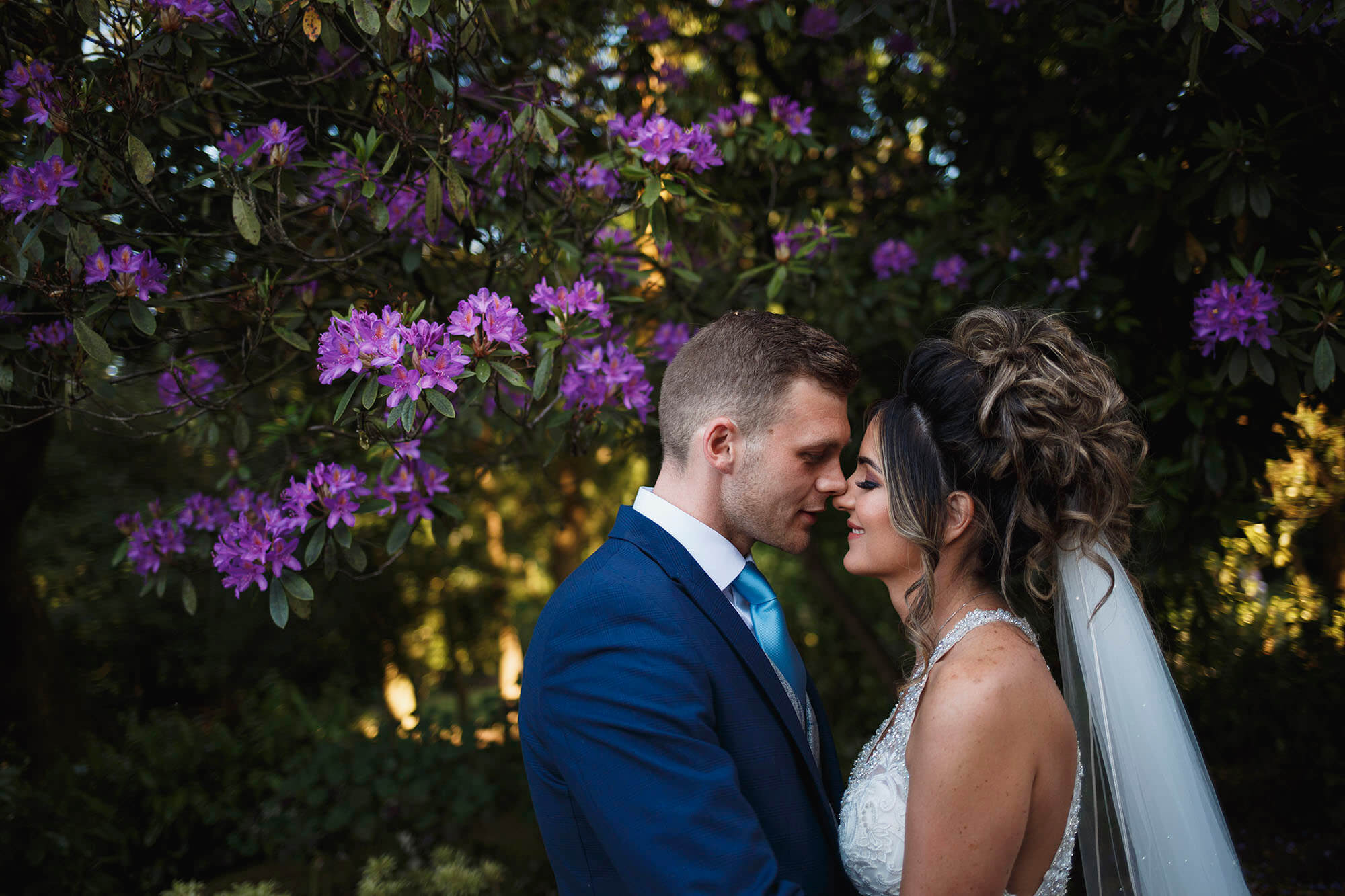 couple kissing near purple flowers