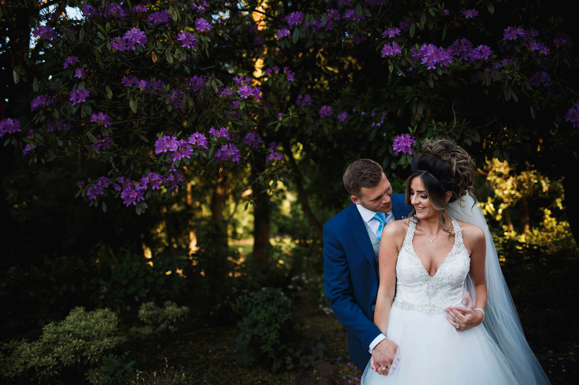 hugging near purple flowers in wedding dress
