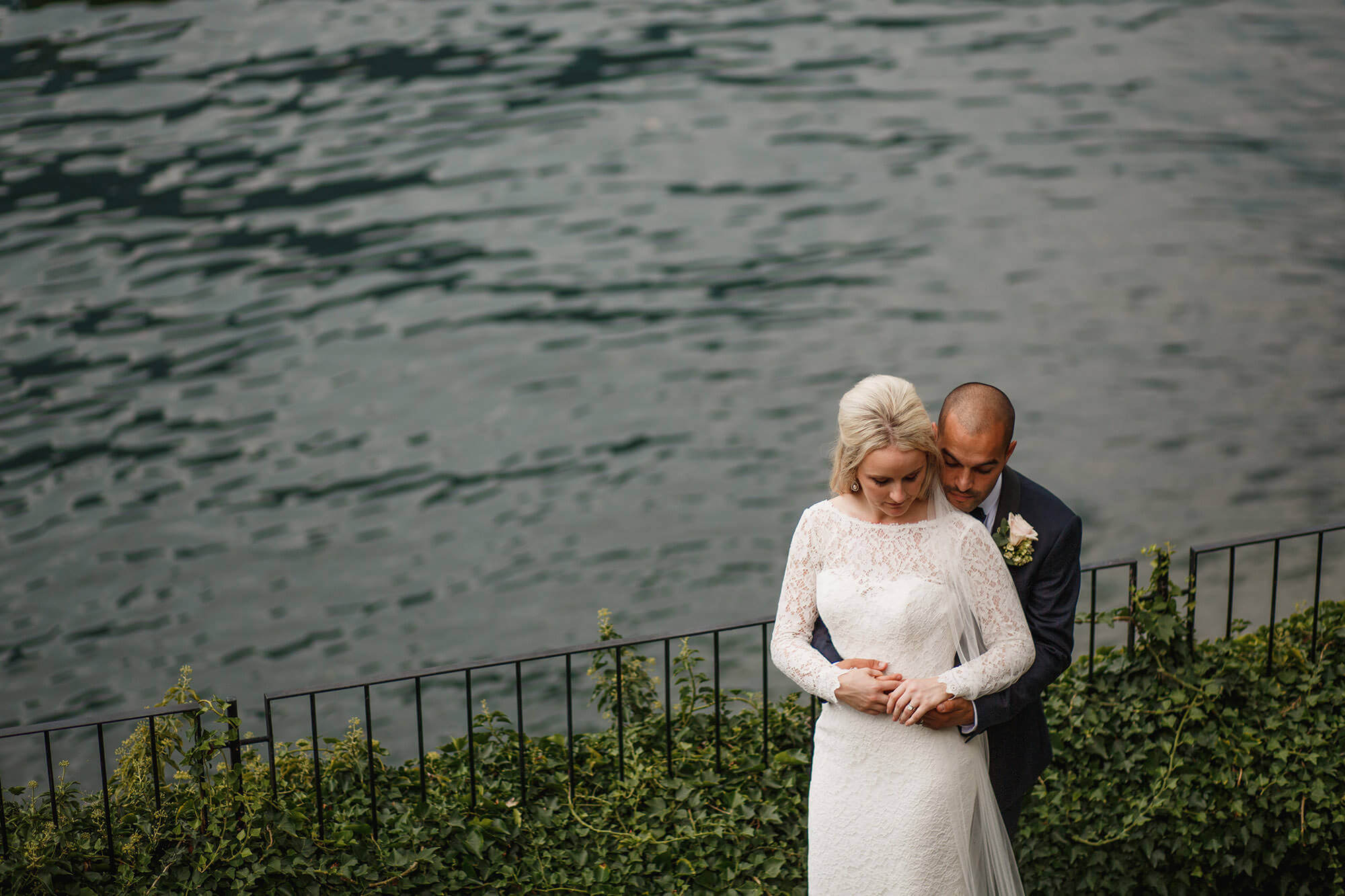 groom hugging bride by lake
