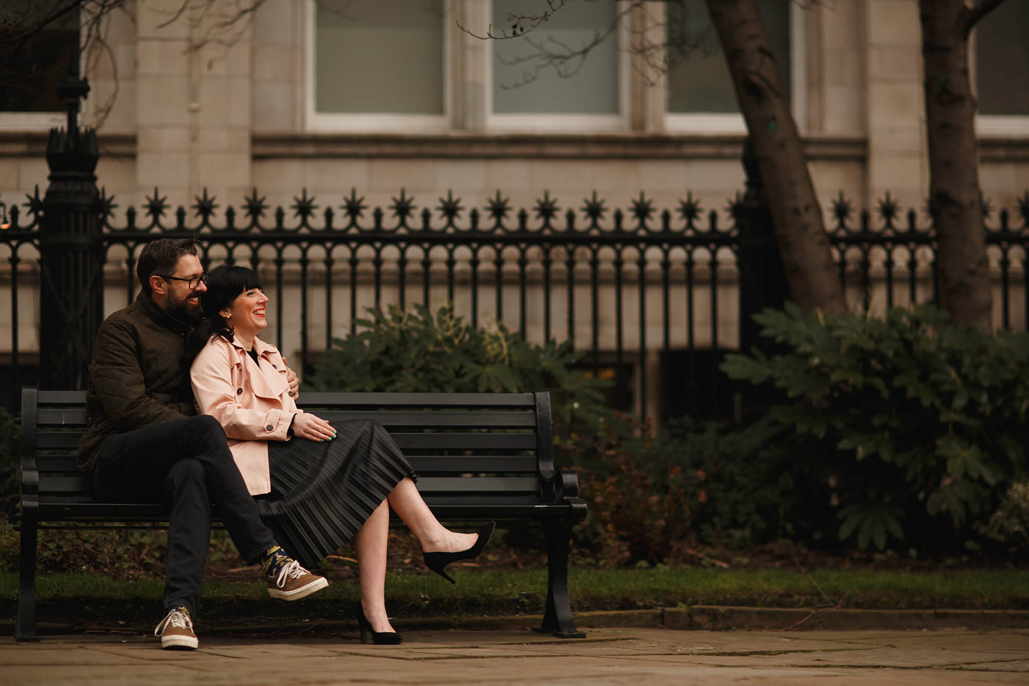 engaged couple sat on bench