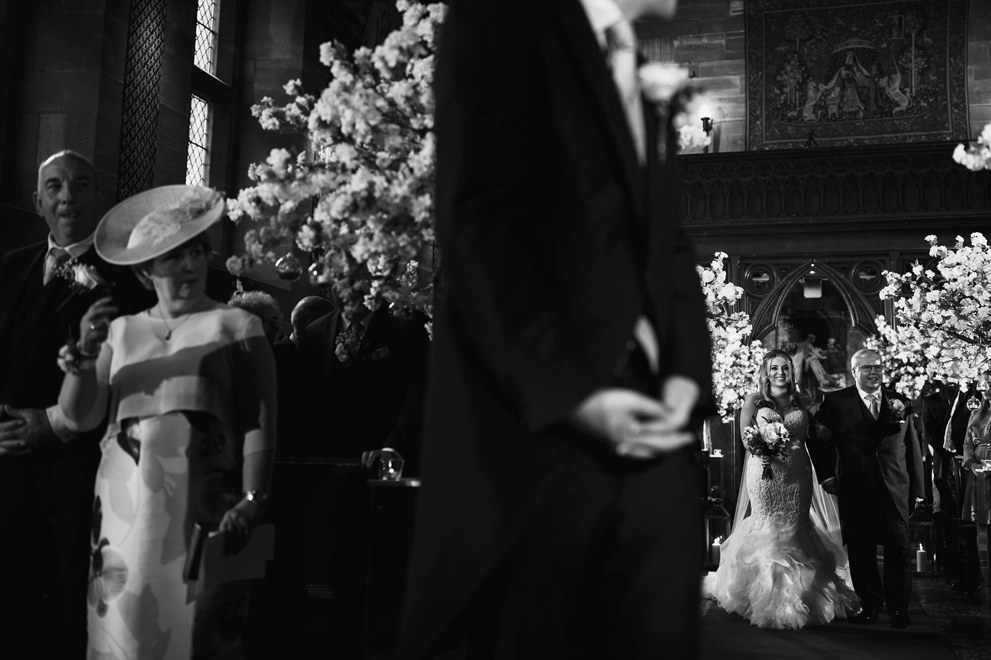 bride walking down the isle in great hall