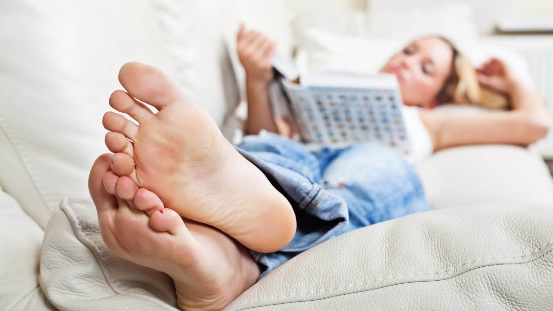 Barefoot young woman lying on sofa and reading book, shallow depth of field, focus on foot soles