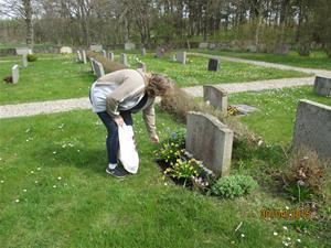 2015 04 30. Min far Eriks grav. Maria kollar blommorna, och gravstenen som behöver tvättas. Fotonr: IMG_1589