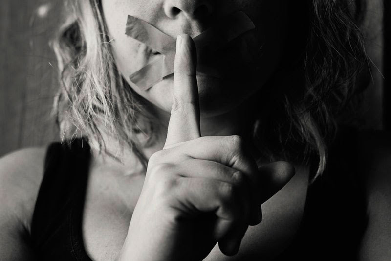 woman with tape over moth and finger to mouth in shush motion