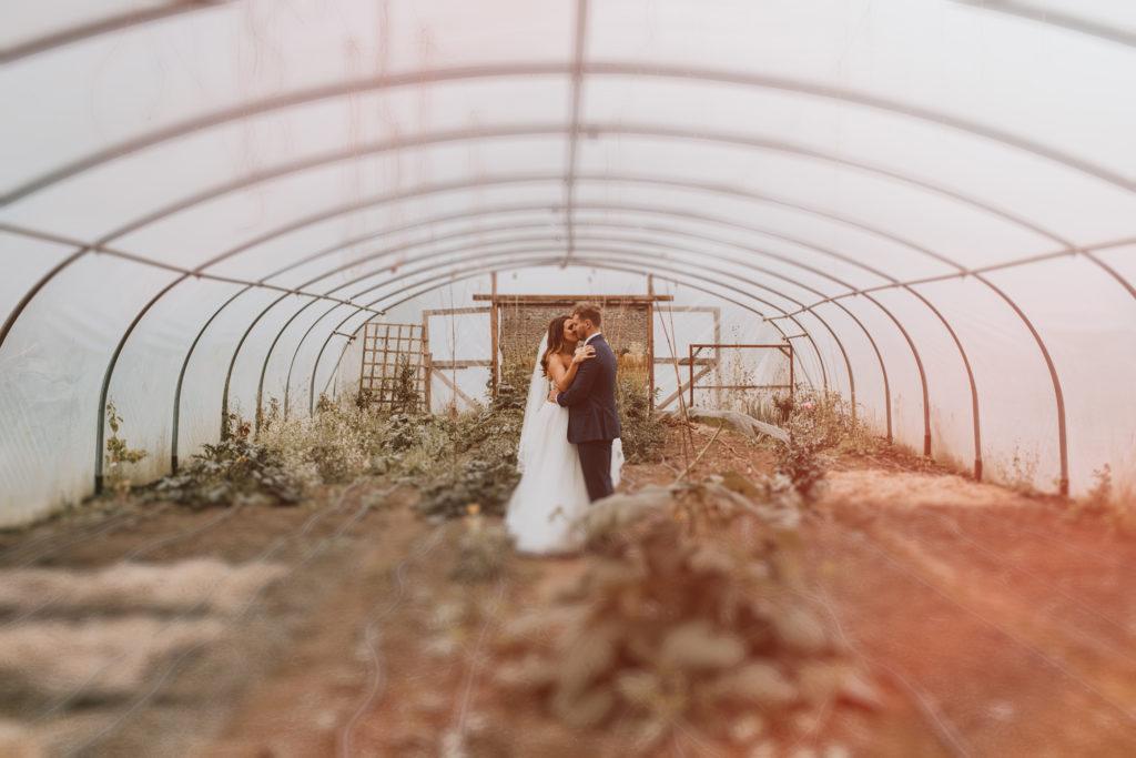 Orla & Gavin kissing in a polytunnel at Cloughjordan House