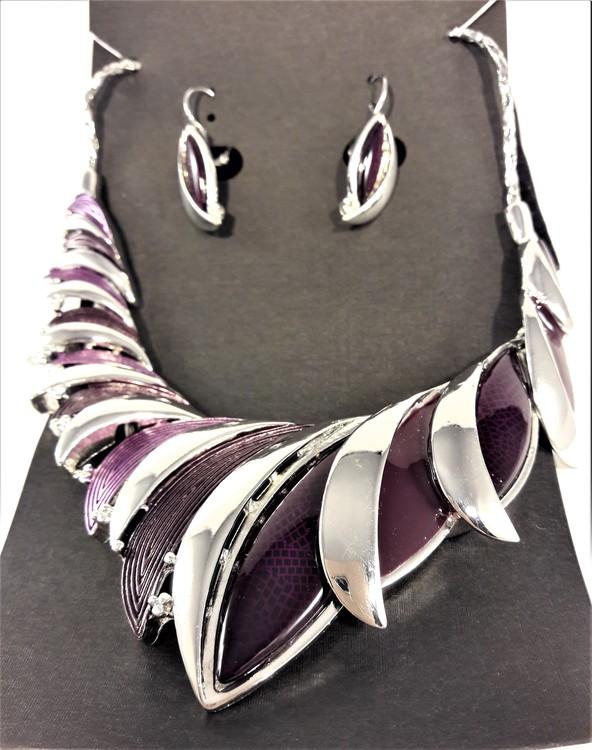 Dekorativt, tungt och vackert lyxhalsband och örhängen med vackra skimrande stenar i lila