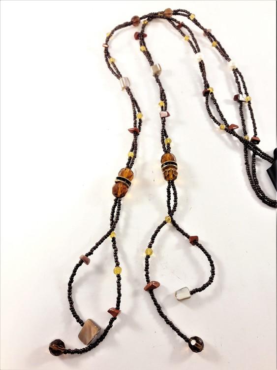 Öppet brunt halsband med små och stora pärlor och stenar i brunt samt glittrande strass