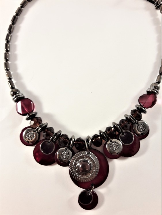 Detaljrikt halsband med många lila och silverfärgade detaljer