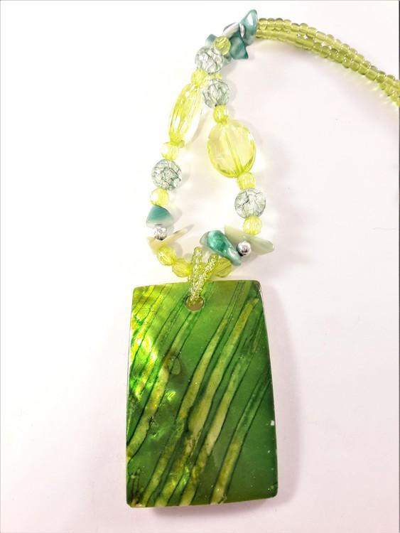 Halsband med gröna detaljer och snäckskal