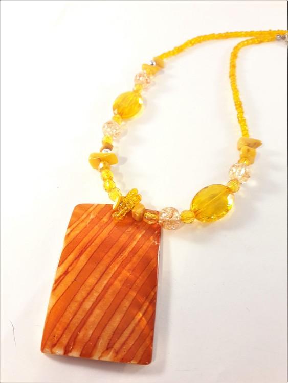 Halsband med orange detaljer och snäckskal