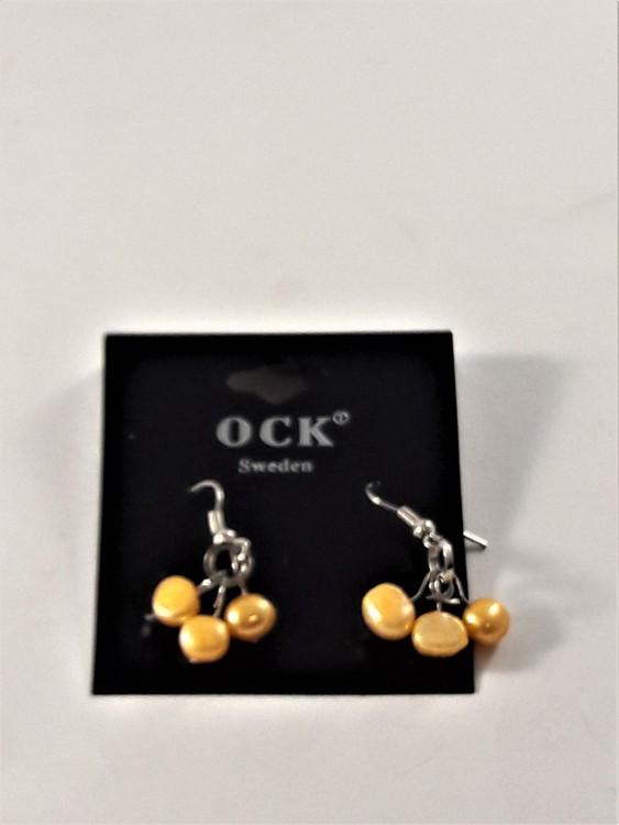 Örhänge med orange detaljer i hänget