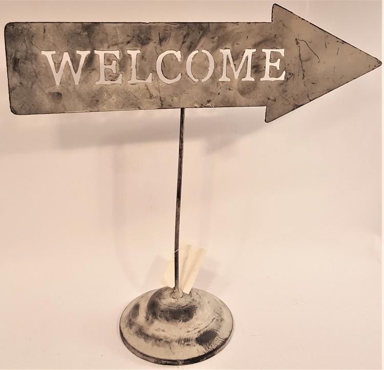 "Plåtpil med texten ""Welcome""."