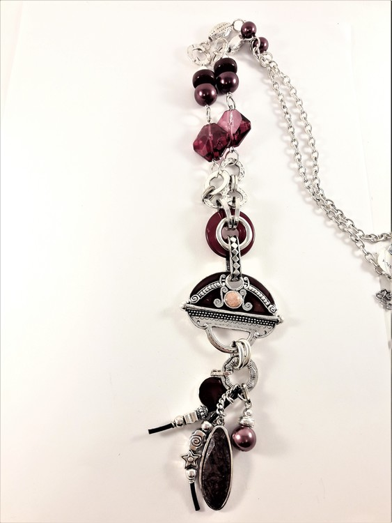 Detaljrikt halsband med kedja och många lila och silverfärgade detaljer