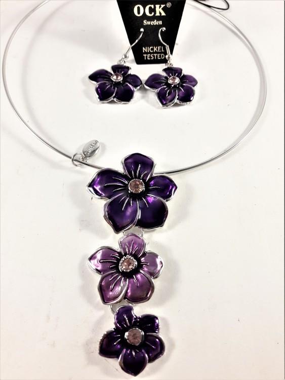 Stelt halsband med hänge av lila blommor samt matchande örhängen