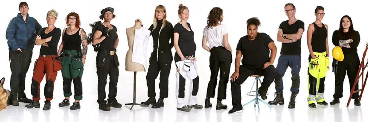 Många kvinnor står på rad och visar sina arbetskläder