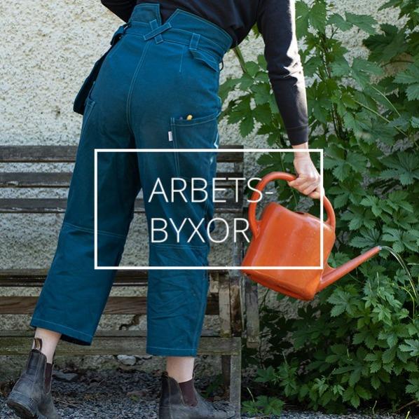 En kvinnlig trädgårdsmästare rensar ogräs i växthuset, iklädd gröna arbetsbyxor