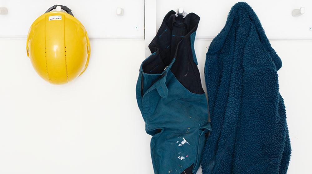 Arbetskläder och skyddshjälm hänger på en vit vägg
