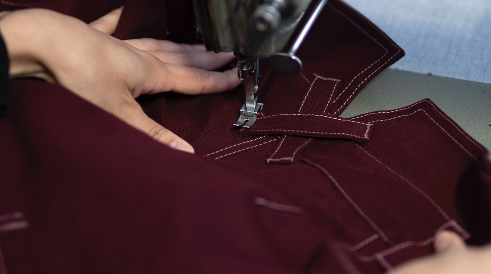 Woman sewing workwear trousers for women