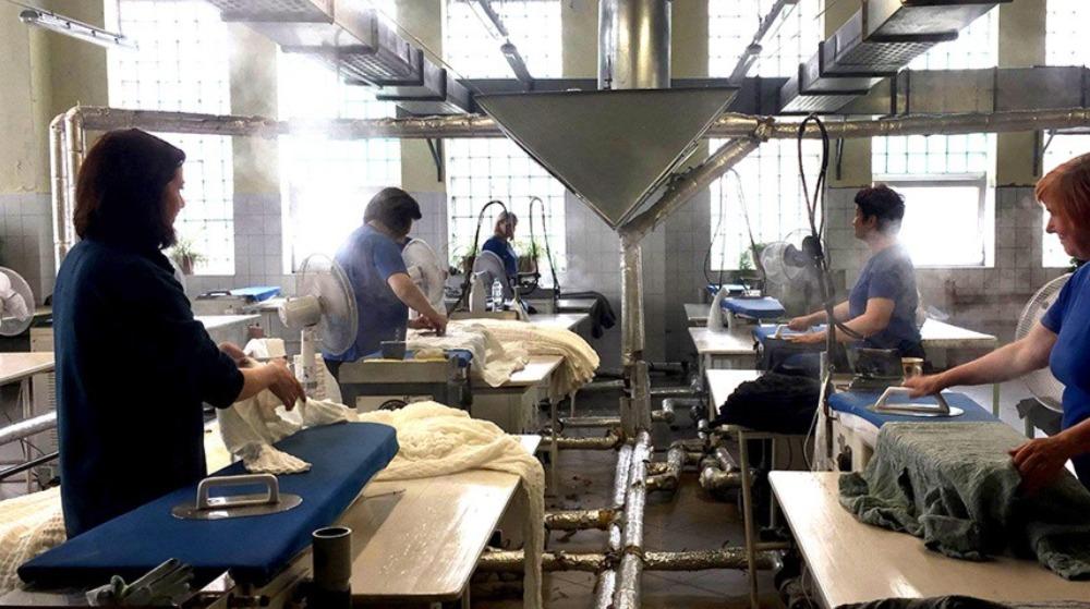Kvinnor står på en fabrik och stryker arbetskläder