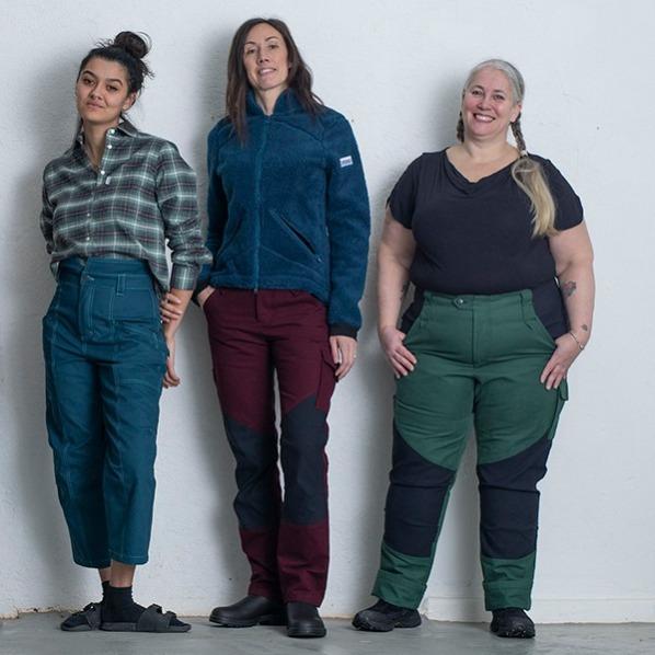 Tre kvinnor som står mot en vägg och har olika arbetskläder för kvinnor