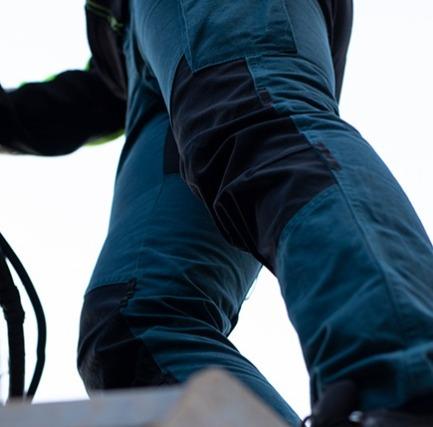 Kvinna iklädd arbetsbyxor från Operose står på ett tak