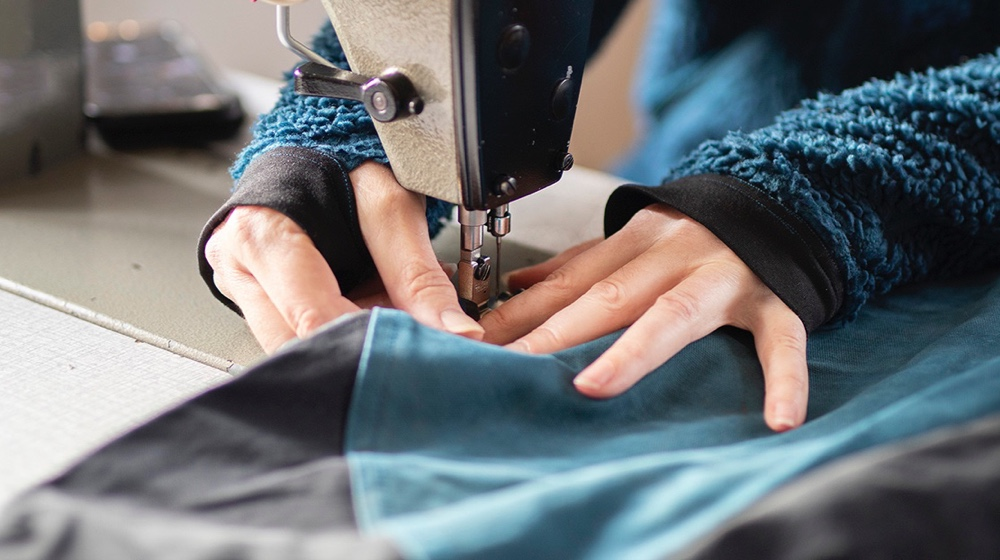 Woman sewing work trousers for women