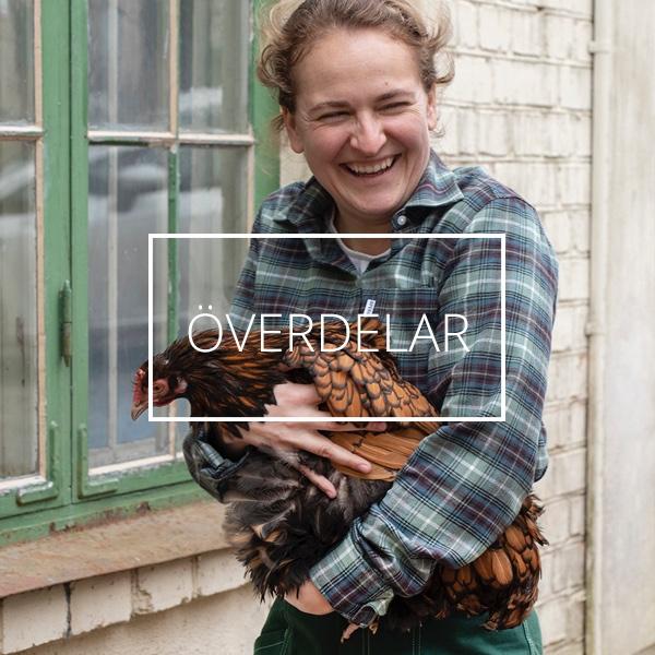 En skrattande kvinna iklädd en grön arbetsskjorta bär en brun höna i famnen.