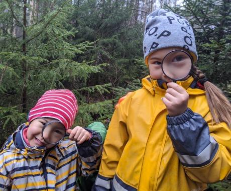 Zwei Kinder im Wald mit Lupe in der Hand