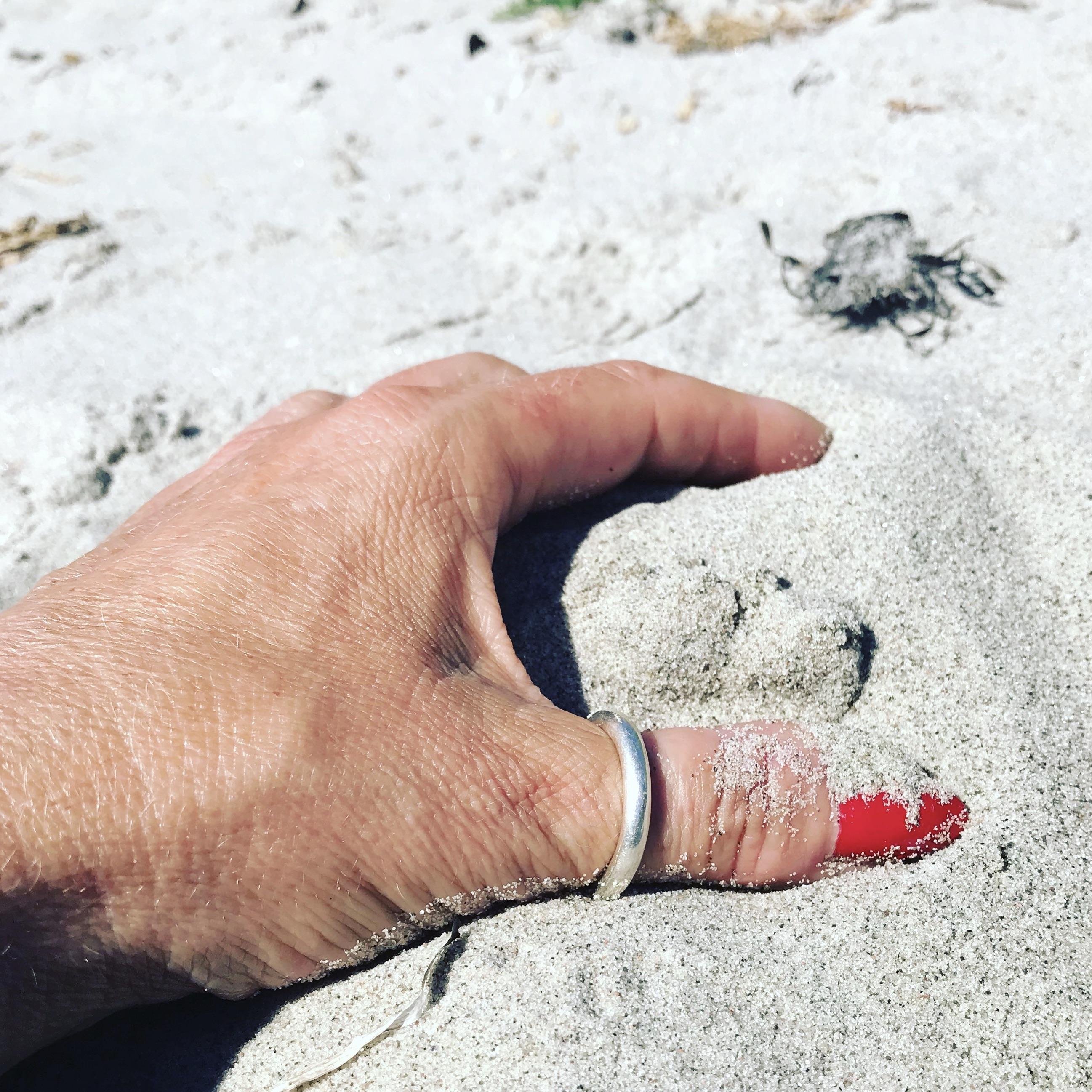 En slät rund silverring på tummen, tumring. A Thin silver ring on the thumb.