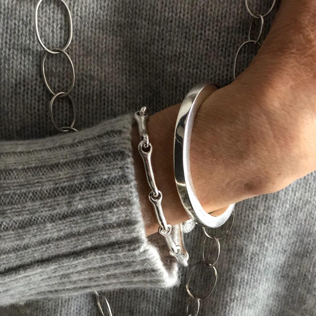 Två silverarmband, en vacker kombination av ett ledat och ett stelt armband. Two silver bracelets together, a beautiful combination.
