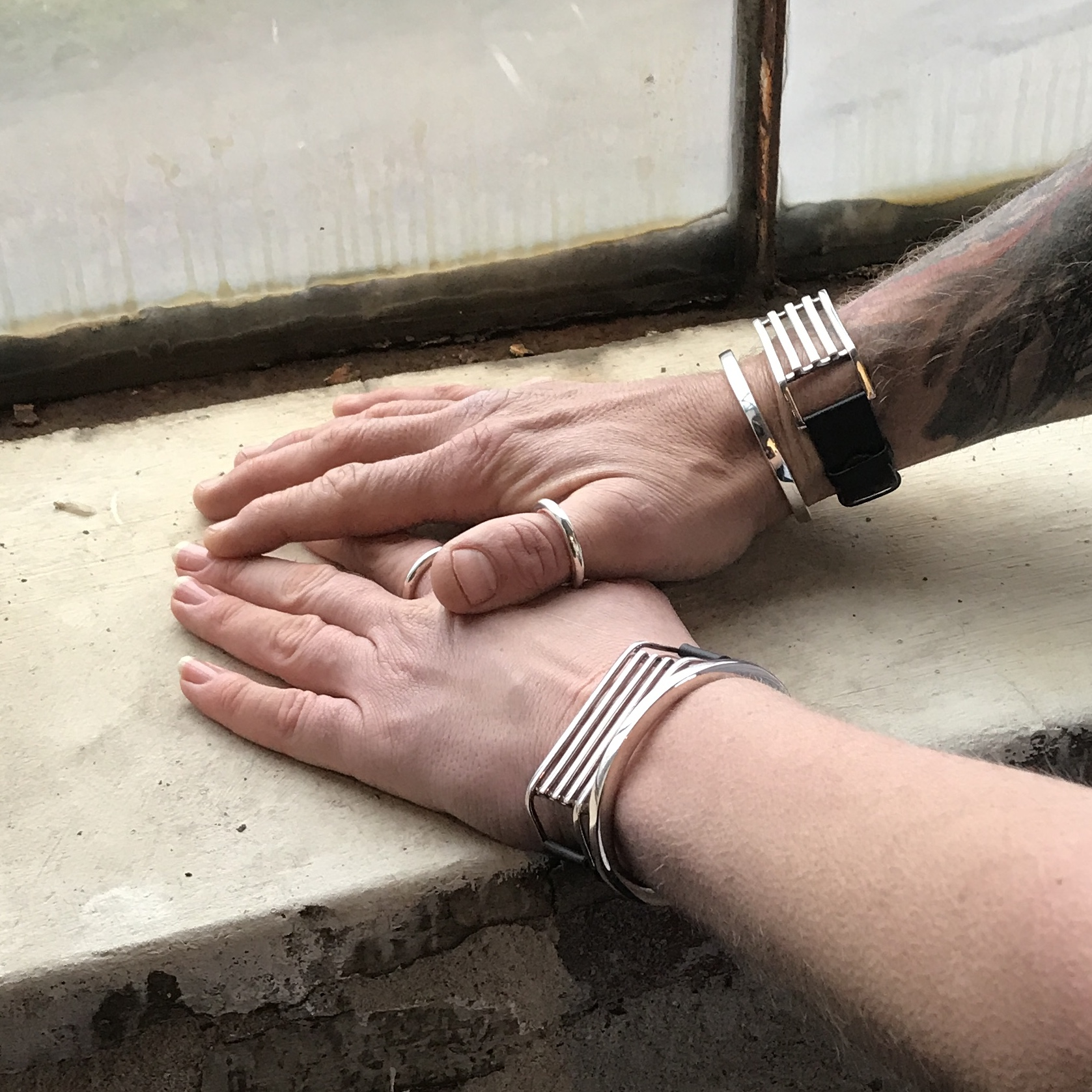 Man och kvinnohand med samma silversmycken, ringar och armband. Hand from man and women wearing same silver jewellery, rings and bracelets.