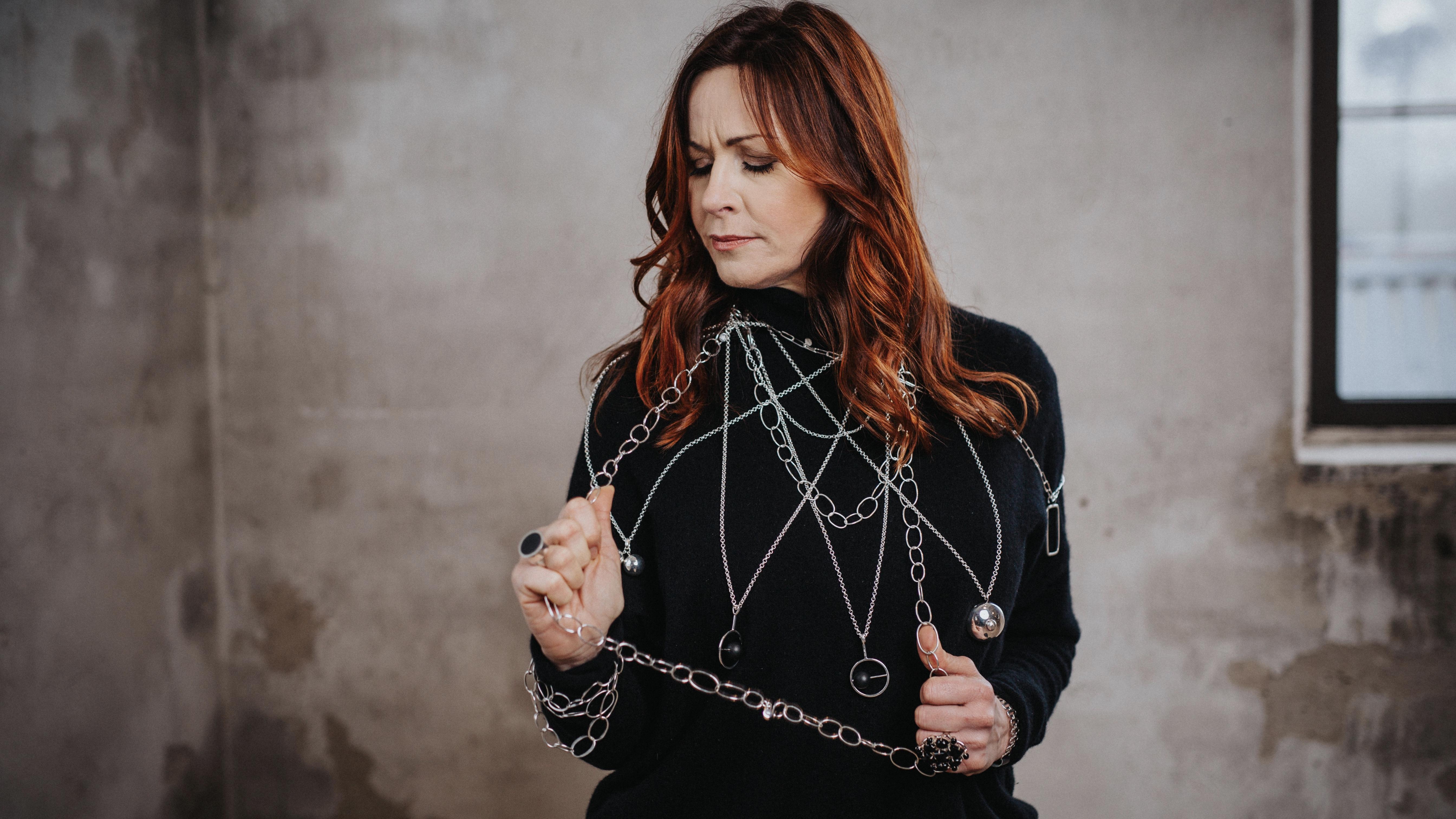 kvinna med massor med långa silverkedjor och silverhängen. woman with many long silver chains and pendants
