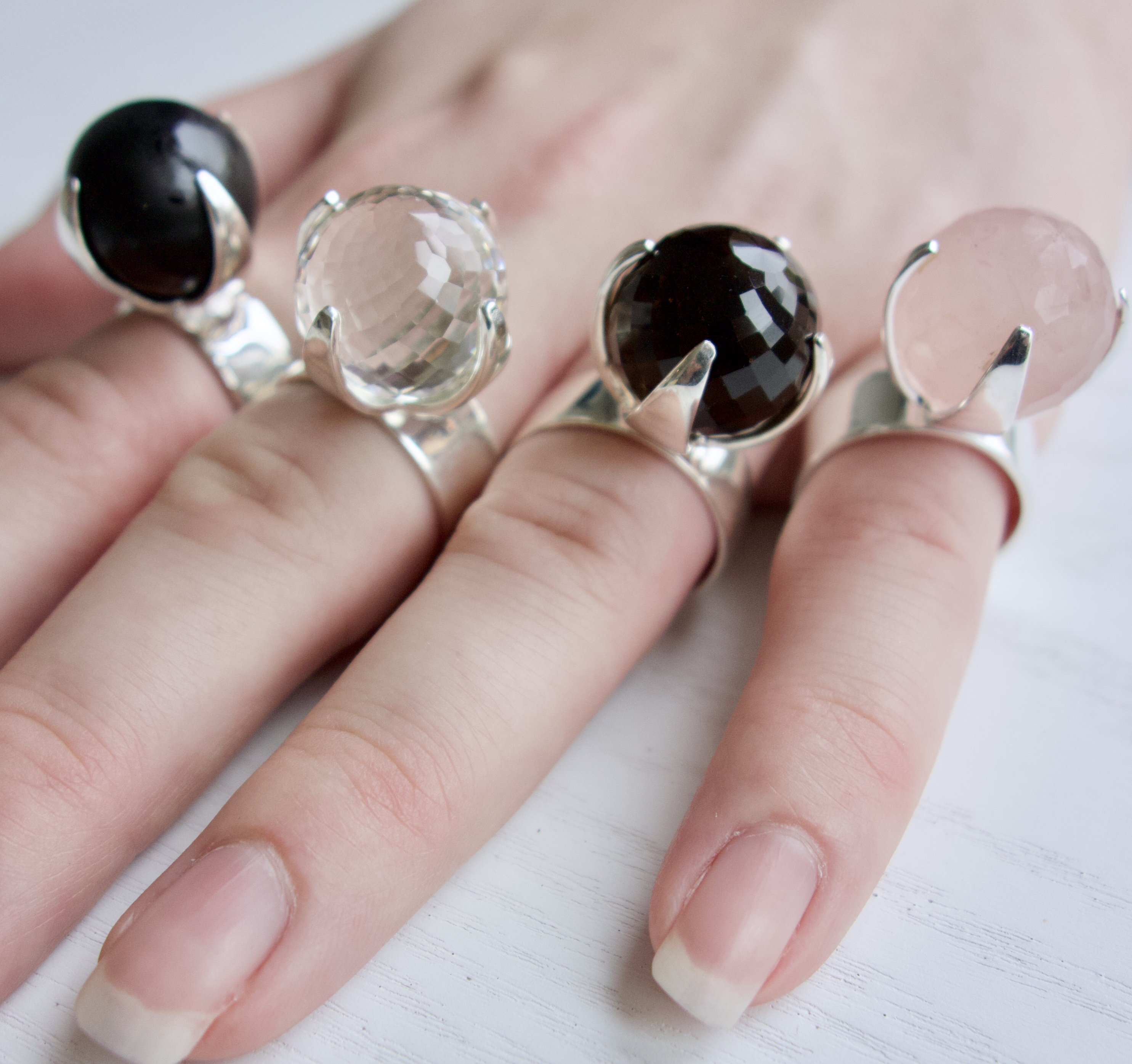Hand med stora ringar och stora stenar; rosenkvarts, bergskristall, rökkvarts och onyx. Hand with big rings with big stones; rose quartz, crystal quartz, smokey quartz and onyx