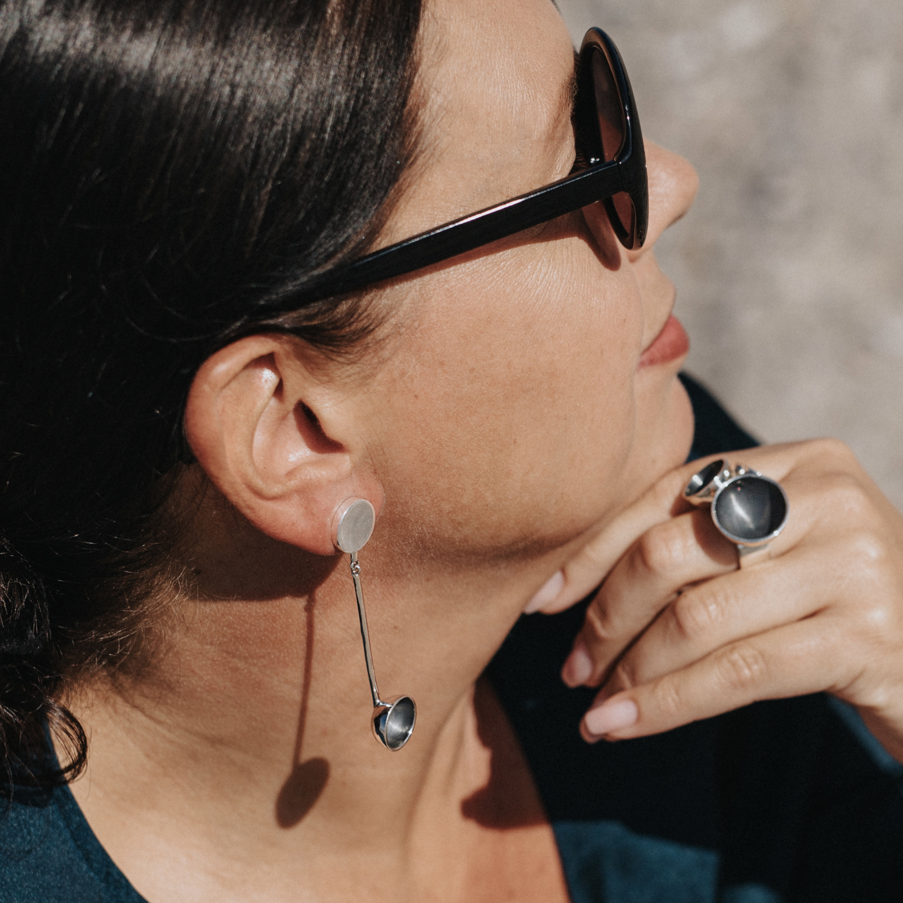 Kvinna med matchande silverring och silverörhängen. Woman with matching set of silver ring and silver earrings.