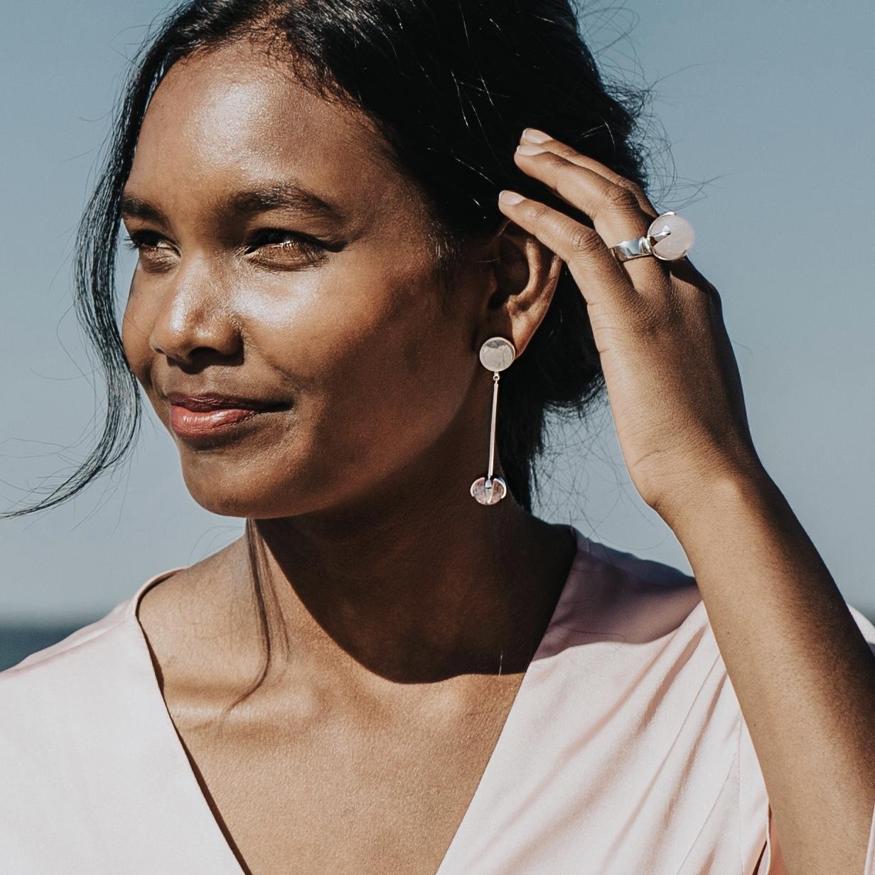 kvinna med stor silverring med rosenkvarts och matchande örhängen. Woman with big silver ring with rose quartz and matching earrings