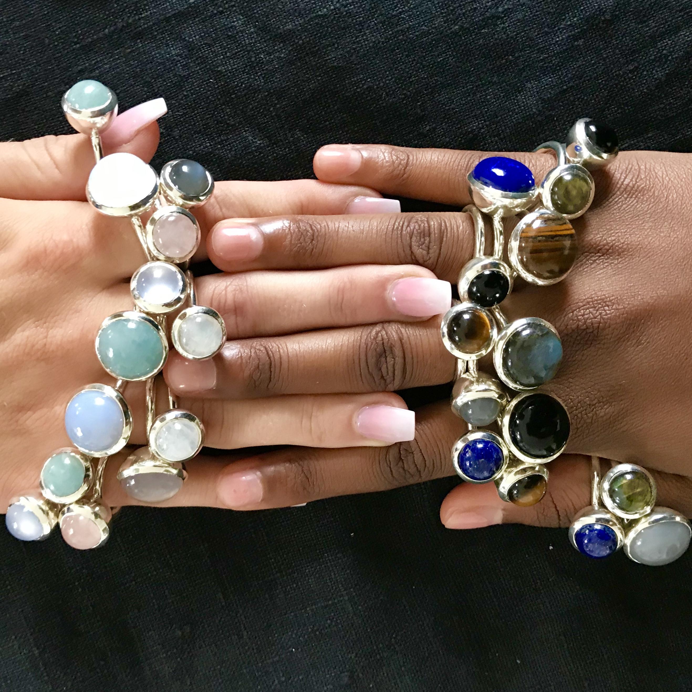 Två händer med massa ringar i olika färger och stenar. Two hands with many various stones and colors.