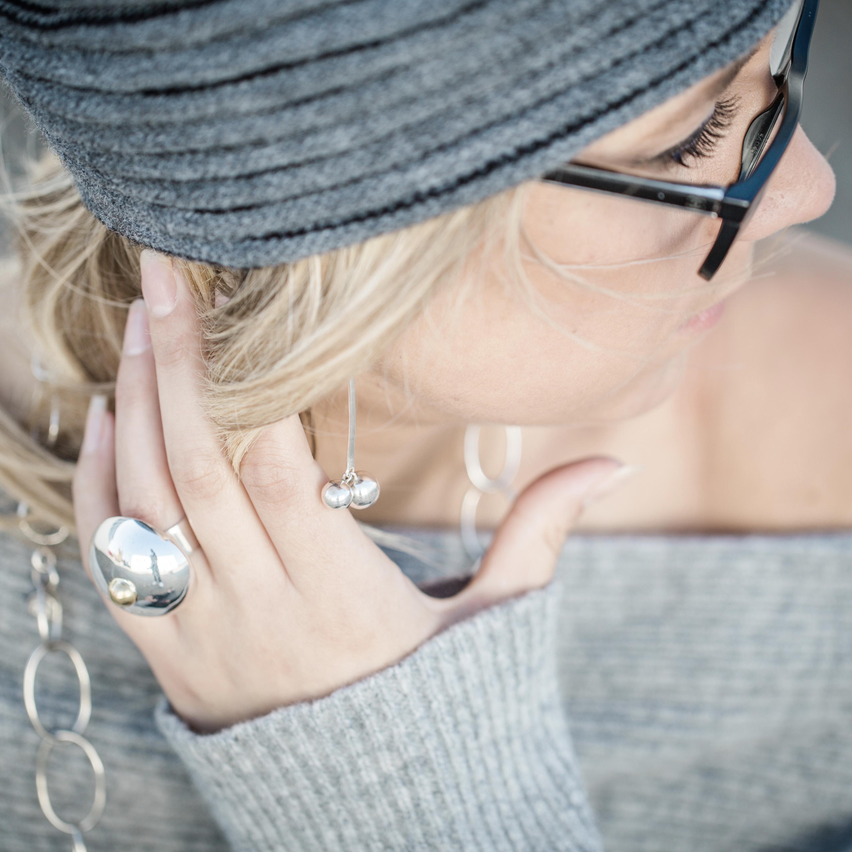 Stor silverring, långa örhängen och en lång silverkedja med oregelbundna öglor. Big silver ring, long earrings, long silver chain.