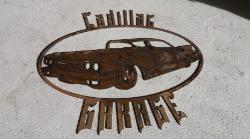 Skylt med en Cadillac och texten Cadillac Garage.