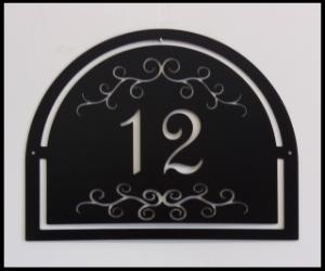 Husnummer skylt, halv-oval mer siffror och krumelurer.