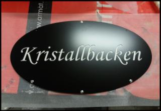 Gårdsskylt Kristallbacken med dubbelplåt och vit text.