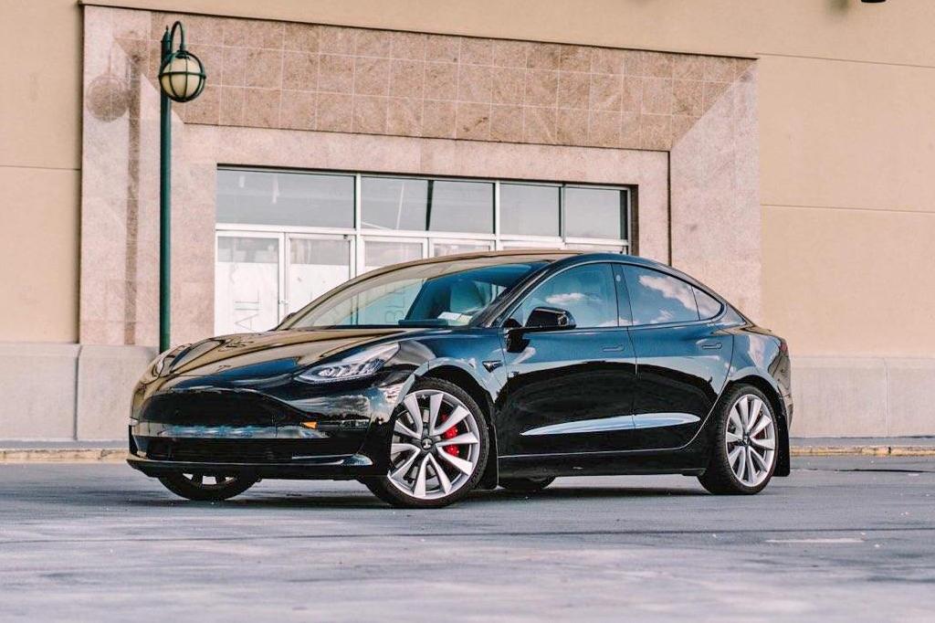 Svart Tesla med svarta stänkskydd