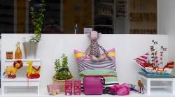 Klotets skyltfönster som visar bredden av sortimentet: inredning, leksaker i trä och tyg, accessoarer, Fairtrade-te, kryddor och sås till matlagning.