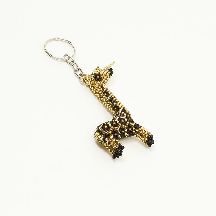 Nyckelring med djurmotiv i form av en giraff. Gjord av många, mycket små glaspärlor. Giraffen är gul och svart, handgjord och rättvist handlad.