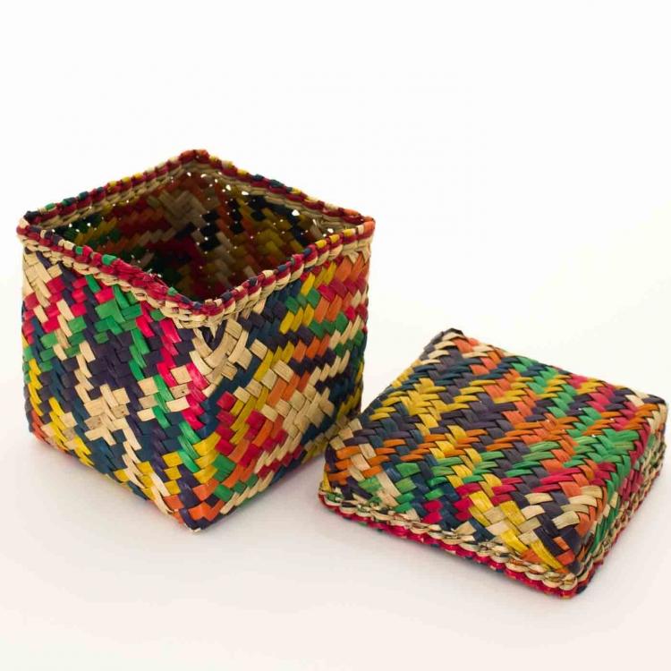 Kubisk korg med lock av, gjord av Patti-gras. Brokigt färgad i orange, gul, grön, röd, mörkblå.