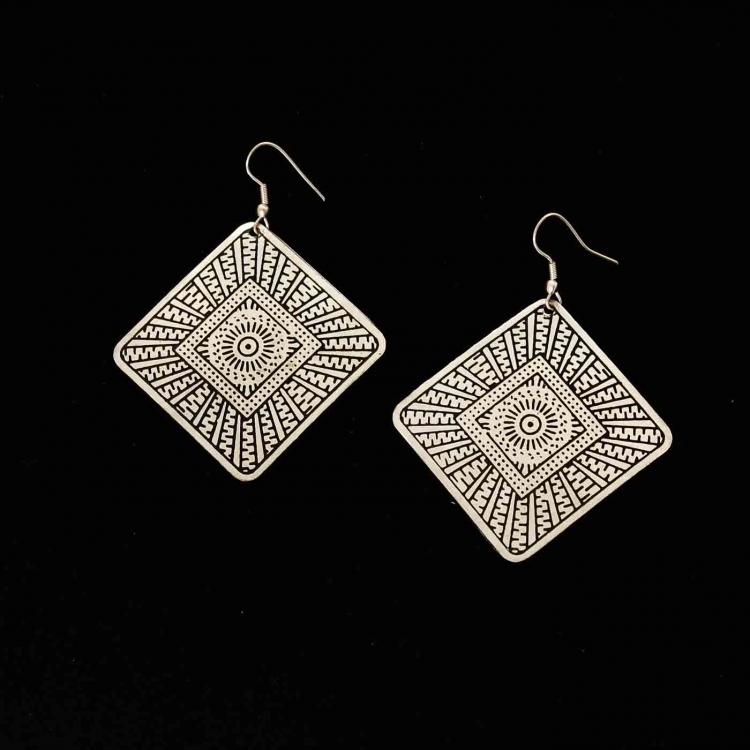 smycke: två örhängen i form av en kvadrat som står på spets. Mönster från utkanten i sicksack, sedan ett mindre kvadrat. Solliknande mönster i mitten.