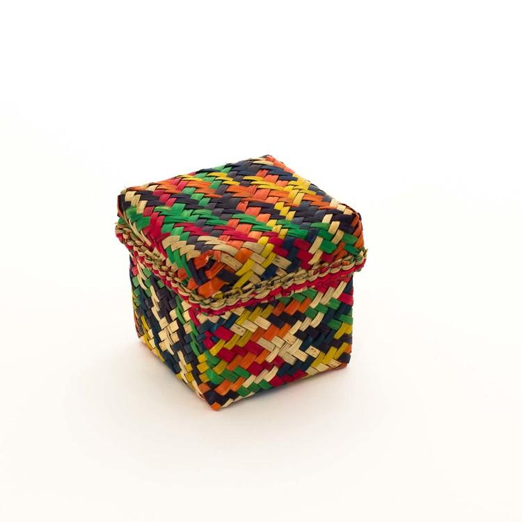 Kubisk korg med lock på. Den är gjord av Patti-gras & brokigt färgad i orange, gul, grön, röd, mörkblå.