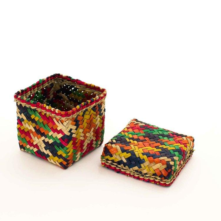 Kubisk korg med lock av. Den är gjord av Patti-gras & brokigt färgad i orange, gul, grön, röd, mörkblå.
