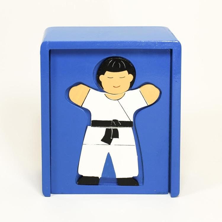 Sluten blå låda med schablon för pussel-läggande. En färdig pusselbild, syns: barn i judoklädsel, Japan.