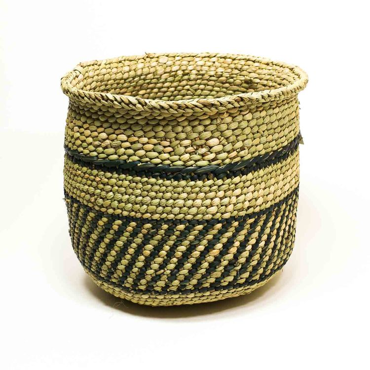 Öppen, flätad korg i naturfärg med enkel mörkgrönt mönster som är typiskt i regionen Iringa i Tanzania.