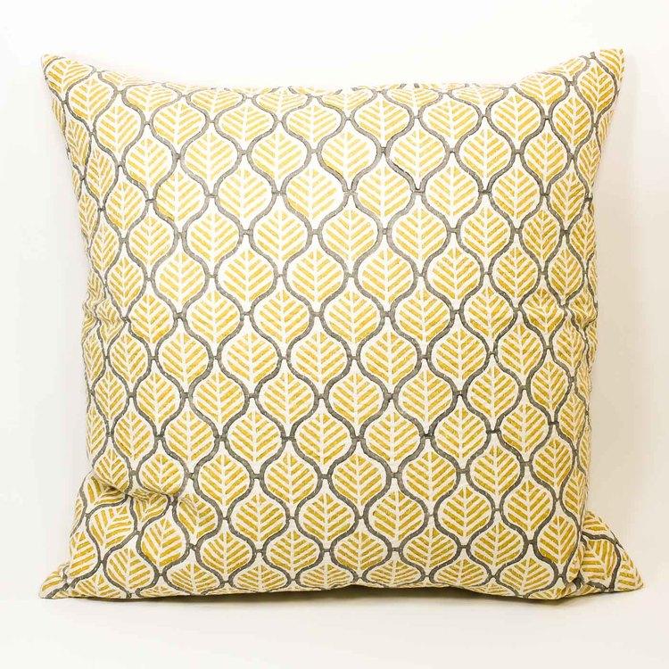 Kudde helmönstrad med gult och grått på vit botten.